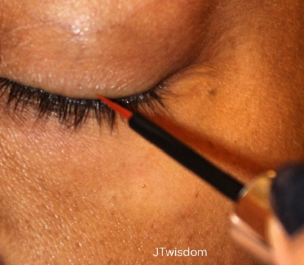JT applying brush to lash area